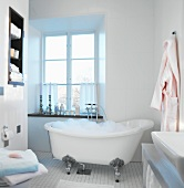 Bathroom with freshly-drawn bubble bath in antique bathtub