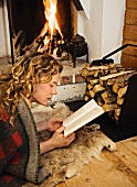 Woman lying in front of fire reading book