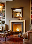 Upholstered footstool in front of open fireplace with roaring fire