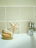 Detail eines Badezimmers mit Seestern und Körperbürste