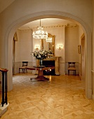 Villa foyer with parquet floor and view of antique table through rounded arch