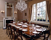 Crystal chandelier above set table in luxurious dining room