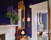 Mirror in blue Baroque frame on blue-painted wall in corner of traditional room