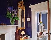 Spiegel im barocken Goldrahmen vor blau getönter Wand in traditioneller Wohnraumecke