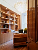 View of wooden bookcase in living room through open door