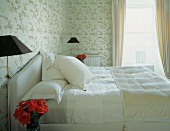 Heller Schlafraum mit Doppelbett vor Fenster