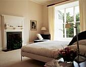 Heller Schlafraum mit modernem Bett vor offenem Kamin