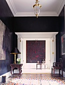 Antique furniture in corner of elegant, traditional foyer with dark walls and white stucco ceiling