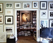 Wall with framed collection of pictures around open doorway with view of library