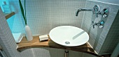 Designer washstand with white, ceramic basin and light grey mosaic wall tiles
