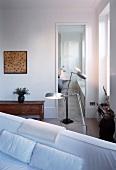 Standard lamps in corner of room in front of glass door with view into bedroom