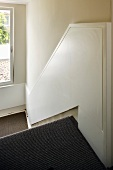 Half-height, white-painted wood panelling on walls of stairwell