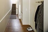 Coat rack in simple hallway with old floorboards