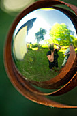 Self-portrait reflected in metal ball in garden