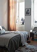 Various bedspreads on bed in front of curtained window
