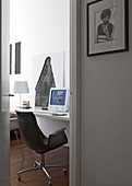 View of retro desk chair at desk with computer through open door