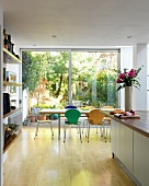Colourful, Bauhaus shell chairs at dining table in front of floor-to-ceiling glass wall with view of garden