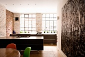 Open-plan kitchen in former factory premises with brick wall