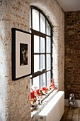 Brick interior wall and window with black metal glazing bars