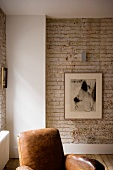 Exposed brick wall in corner of living room and part of a leather armchair