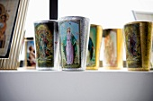 Collection of beakers with printed pictures of saints