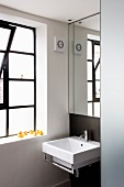 Mirror above designer washstand in niche with window