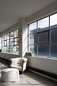 Baroque armchair and modern stool below industrial window in loft apartment