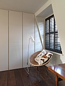 Circular, rattan shell chair with cushion below window with closed shutters