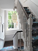 Staircase with turned balusters and patterned runner on stairs
