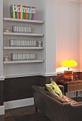 Wall niche with fitted shelving above stucco frieze painted dark brown