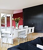 White designer dining table and chairs in front of black fitted cupboard in modern living-dining room