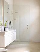 Modernes Bad mit Glastrennwand vor Dusche