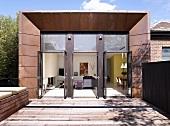 Modernes Wohnhaus mit offen stehenden Glastüren und Holzterrasse