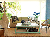 Colourful painted coffee table on sisal rug and rattan furniture in living room