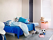 Bed with blue bedspread and toys on the floor in a small children's room