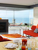 Designer living room with glass walls with a view of a terrace and the ocean beyond