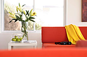 Bouquet of lilies next to an orange designer sofa with yellow throw and telescope