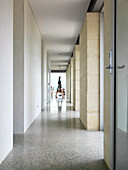 Bright hallway between doors and windows with natural stone walls