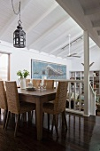 Dining table and rattan chairs on gallery with view into interior