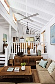 Antique coffee table, simple sofa and gallery in open-plan interior of house with white wooden ceiling