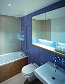 Mirrored cabinet in niche of wall with blue mosaic tiles in modern bathroom