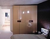 Wardrobe with glossy doors in bedroom and open door with view of hallway