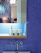 Mirrored cabinet with indirect lighting and shelf on wall with blue mosaic tiles