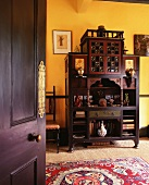 View of Oriental dark wood cupboard against yellow-painted wall through open door
