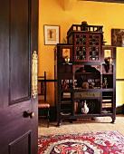 View of Oriental dark wood cupboard against yellow-painted wall through open door