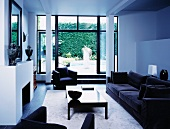 Black sofa set in white, modern living room with view of terrace
