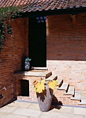 Brick house and entrance steps and ceramic pot with autumn leaves