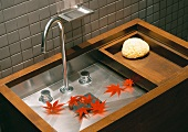 Red autumn leaves lie in minimalist designer sink in wood and stainless steel