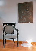 Baroque chair with upholstered back and seat next to modern floor lamp