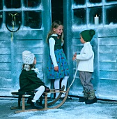 Three children with sledge in front of house